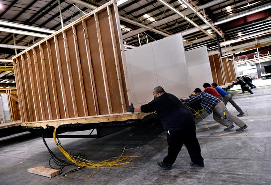 Workers at New Vision Manufacturing in Breckenridge push one of their modular living units to its next station Nov. 28.