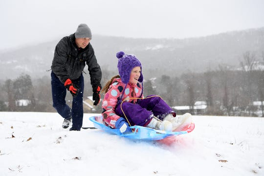 Nariah Tracey pushes his daughter, Molly, 9, down a hill on a sled near their home in Haw Creek on Dec. 9, 2018.
