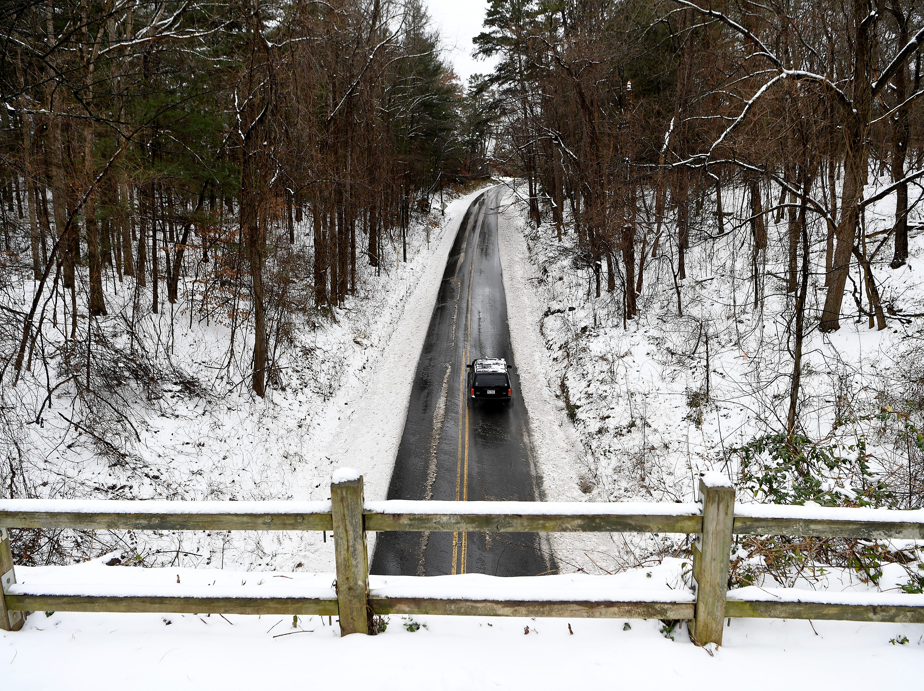 A car drives up Riceville Road as seen from the Blue Ridge Parkway after a snow on Dec. 9, 2018.
