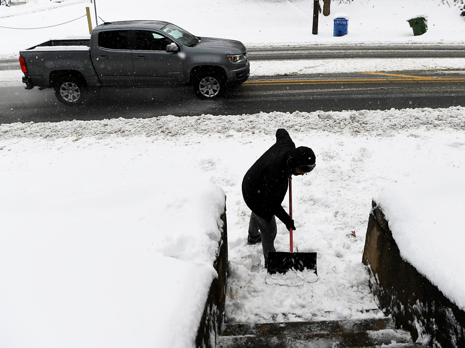 Stephen Collins shovels the stairs in front of his home in West Asheville Dec. 9, 2018.