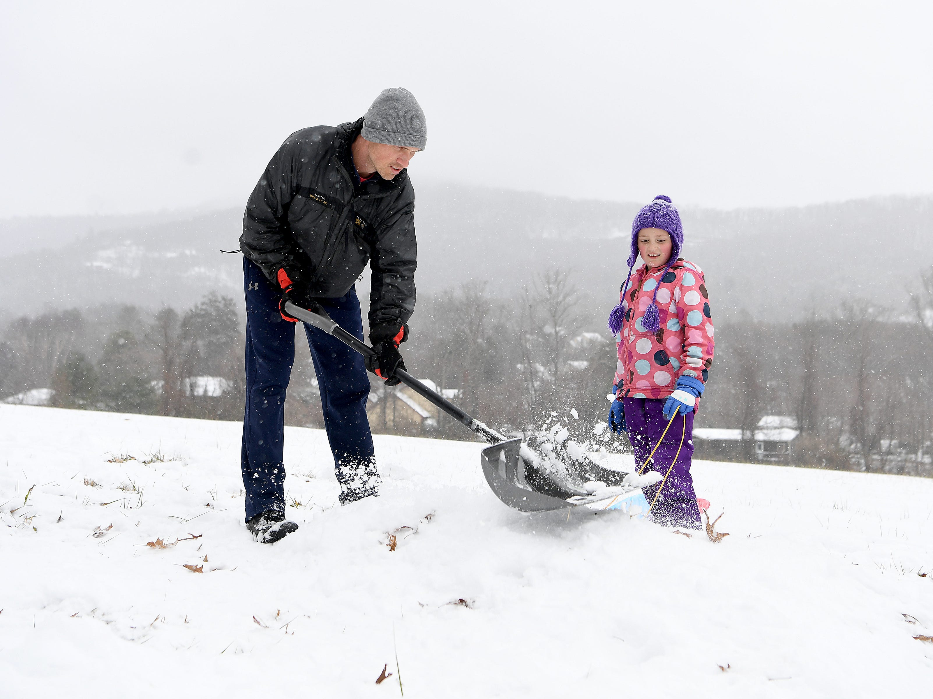 Nariah Tracey uses a shovel to pack down a snow mound so his daughter, Molly, 9, can sled near their home in Haw Creek on Dec. 9, 2018.