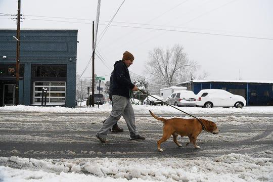 Pedestrians walk on Haywood Road to bypass snow-covered sidewalks in West Asheville Dec. 9, 2018.