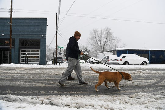 Pedestrians walk on Haywood Road to bypass snow-covered sidewalks in West Asheville Dec. 9, 2018.