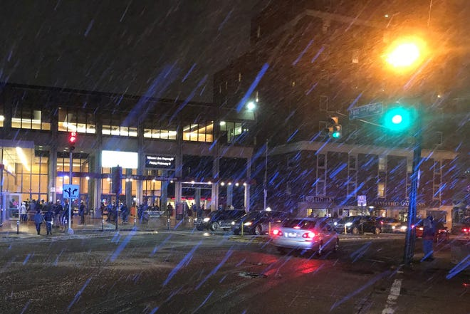 Streets in downtown Asheville were getting slushy at 7:40 p.m. Saturday. This shot shows Haywood Street as people make their way into the U.S. Cellular Center for the Warren Haynes Christmas Jam. A city police car's light turns some of the snow blue.