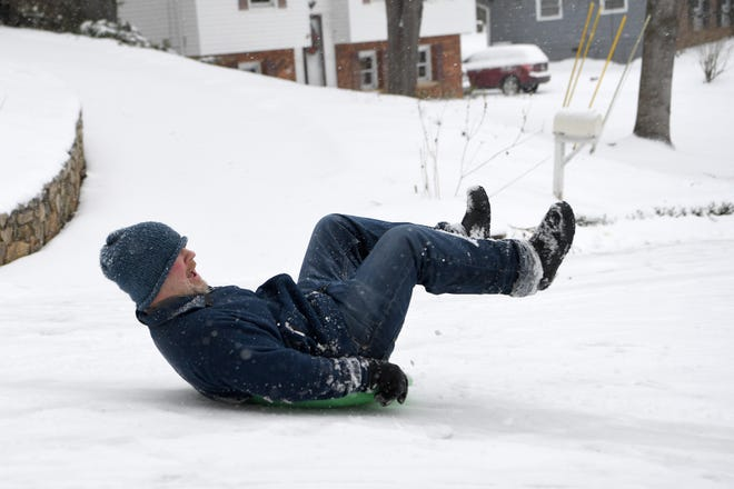 Chris Howes lifts his legs in the air to get some speed as he sleds near his home in Haw Creek on Dec. 9, 2018.