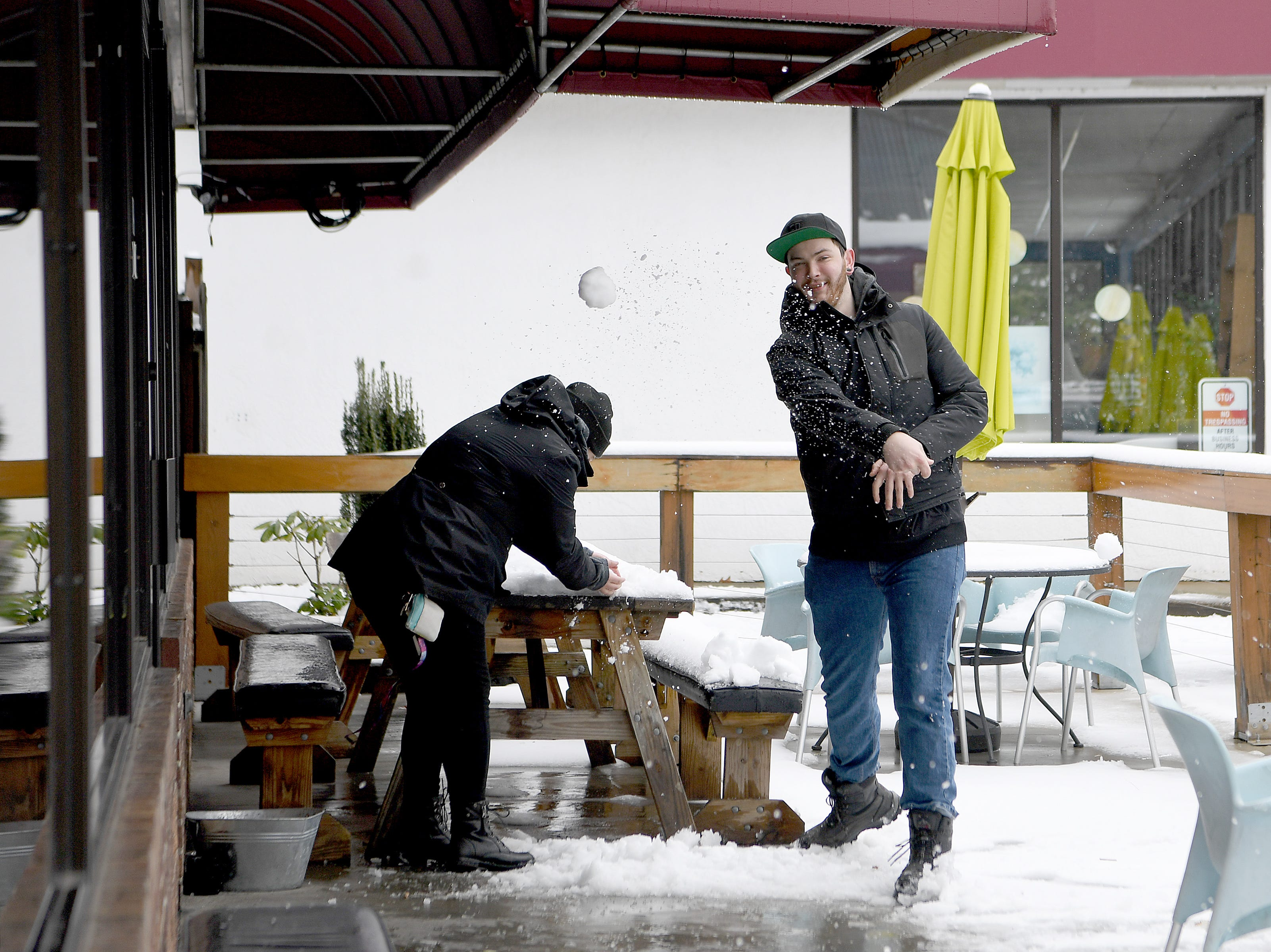 Katie Abney and John Herwig have a snowball fight on the porch of The Social in East Asheville on Dec. 9, 2018.