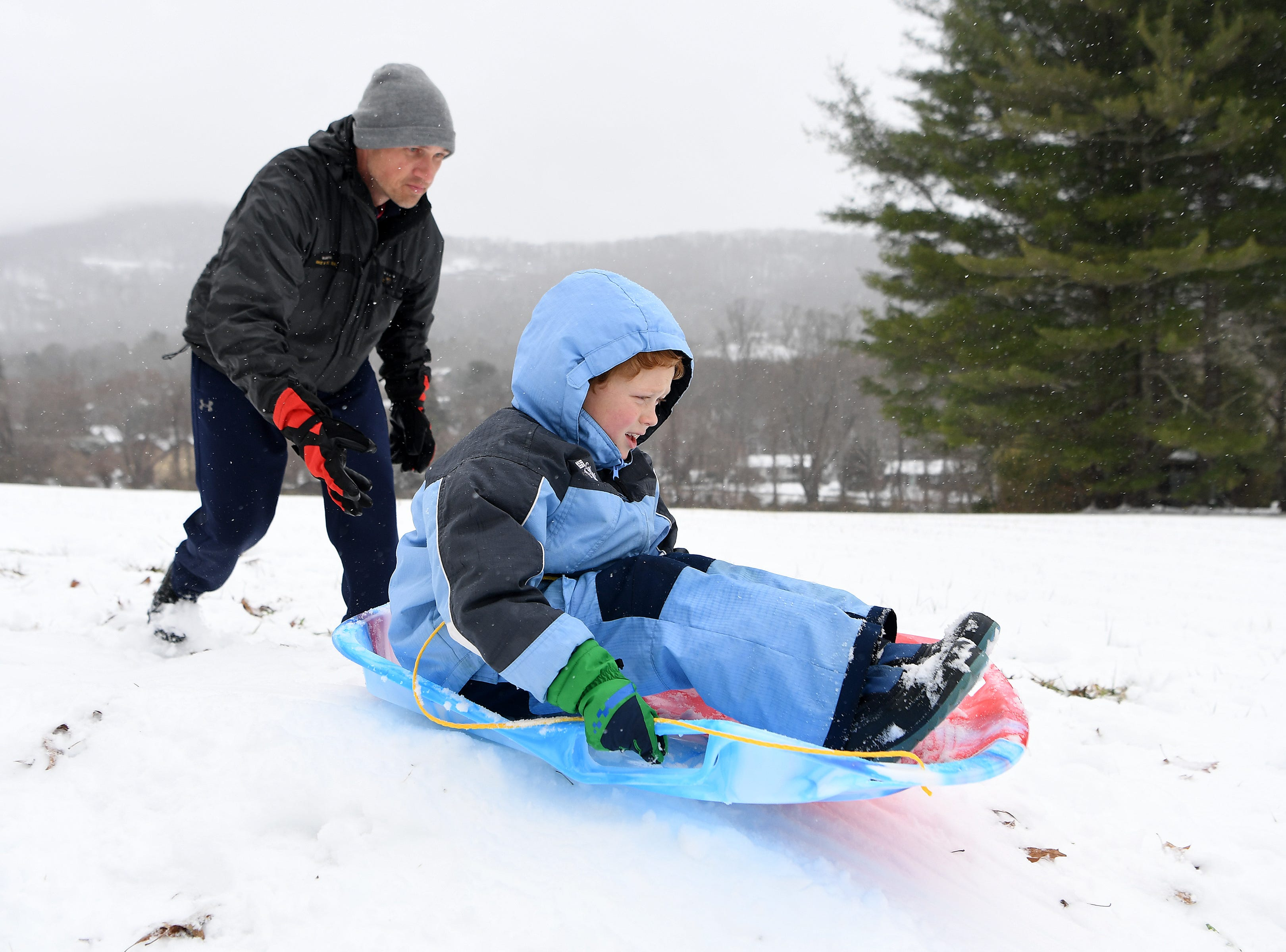 Nariah Tracey pushes his son, Rye, 7, down a hill on a sled near their home in Haw Creek on Dec. 9, 2018.
