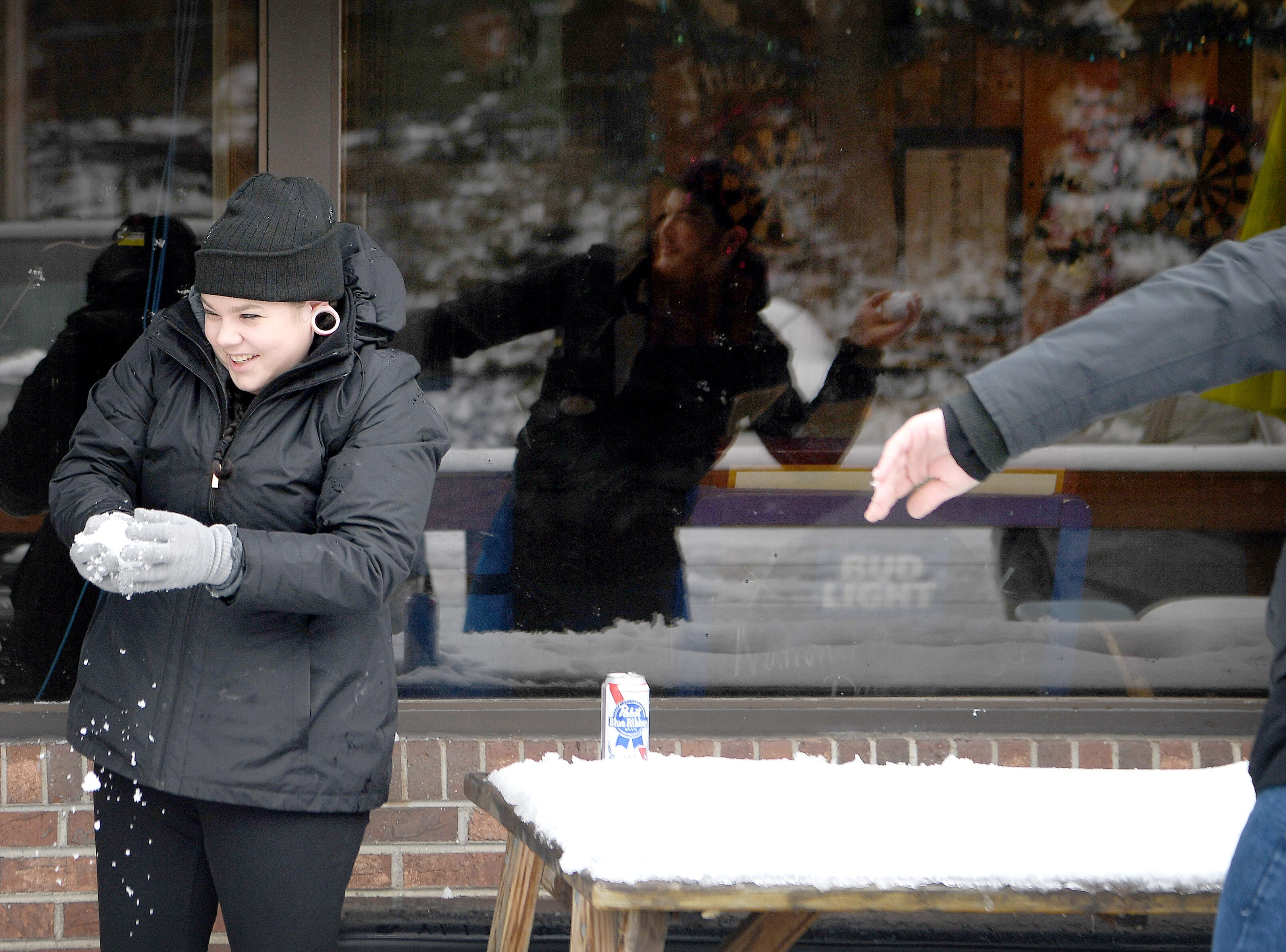 Katie Abney makes a snowball as John Herwig winds up to throw ones as they have a snowball fight on the porch of The Social in East Asheville on Dec. 9, 2018. It was Abney's first time playing in the snow after growing up in Florida.