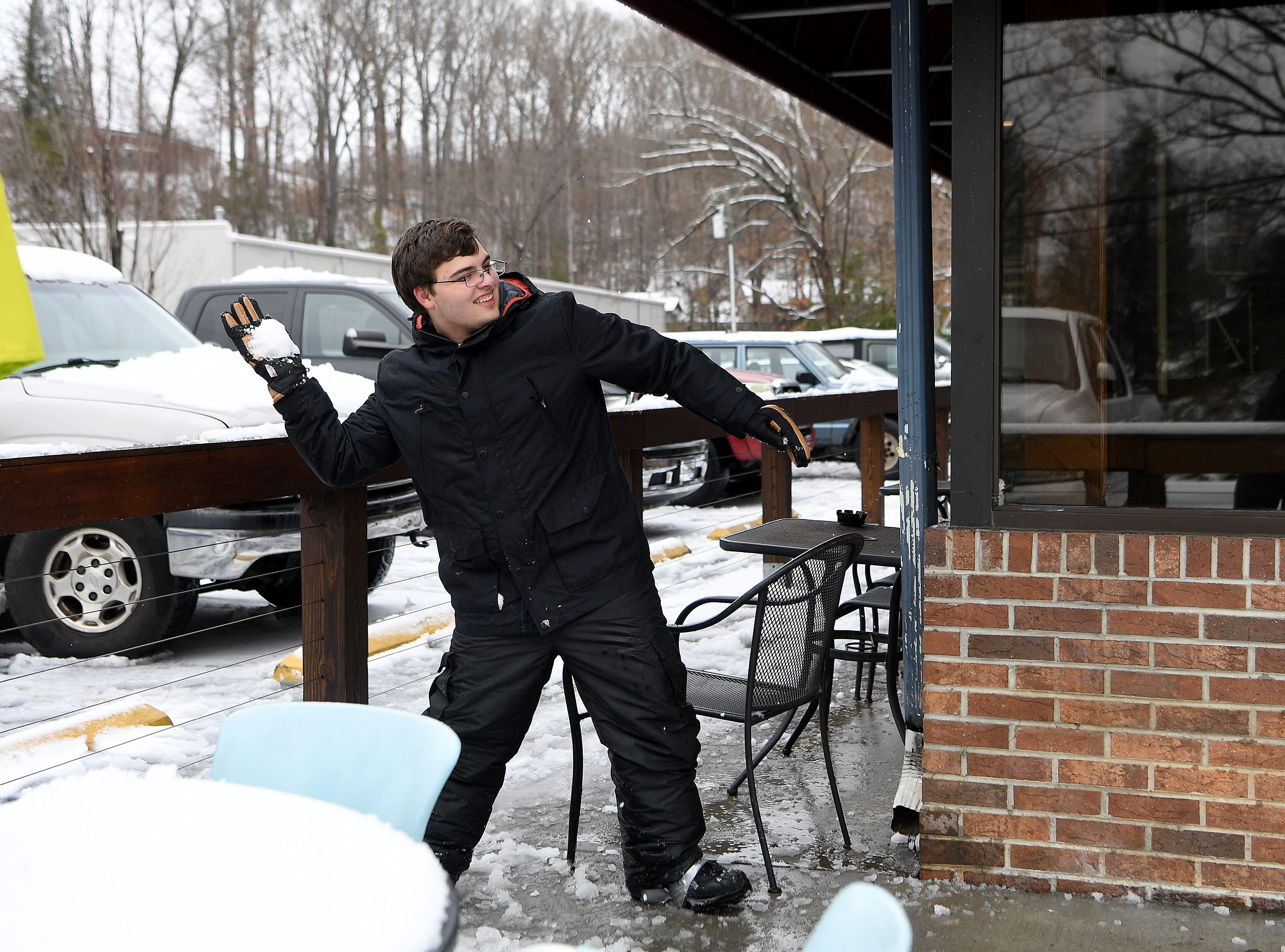 Reece Combs winds up to throw a snowball during a fight on the porch of The Social in East Asheville on Dec. 9, 2018.