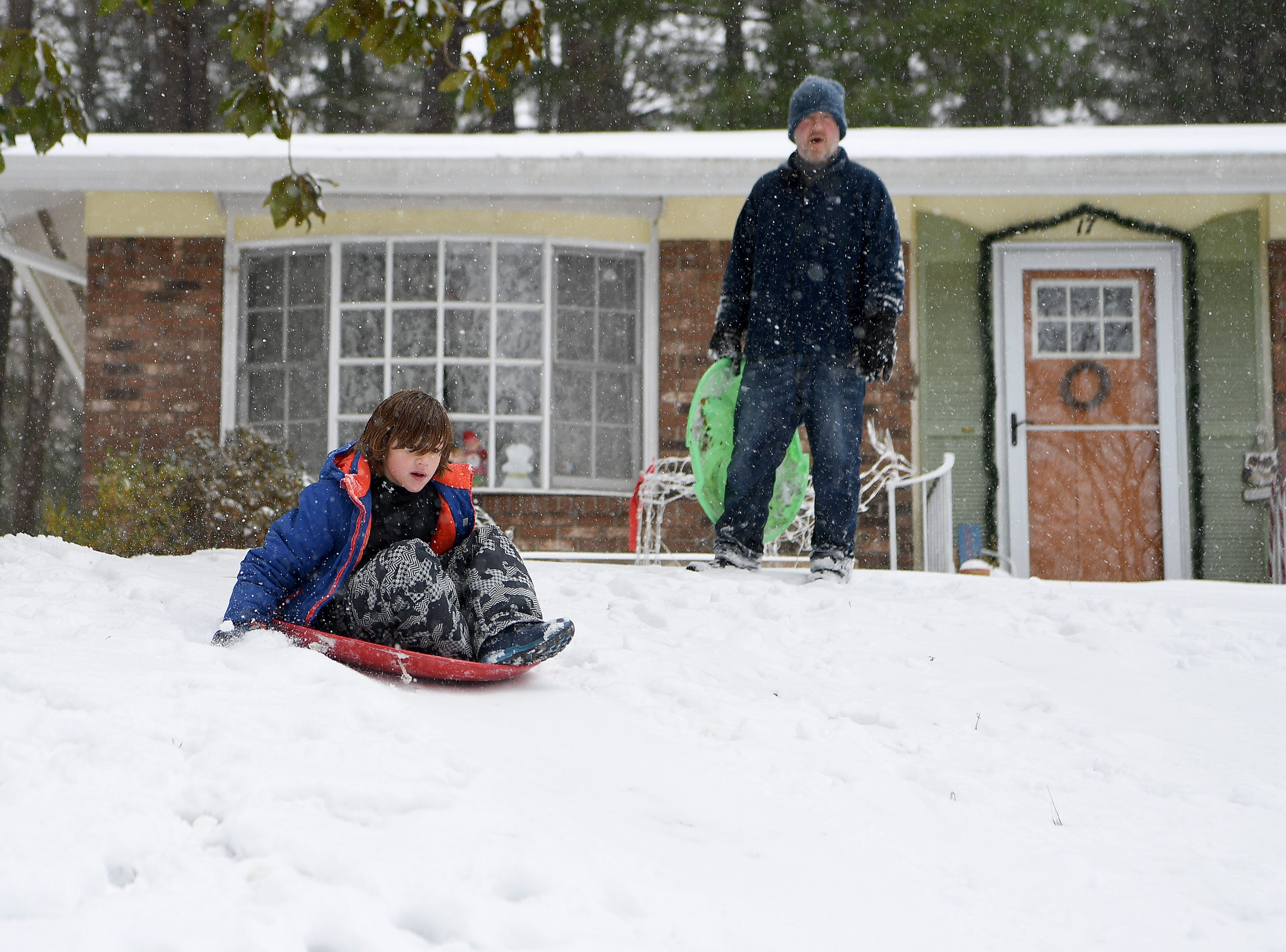 As his dad, Chris, looks on, Dalton Howes, 8, sleds near his home in Haw Creek on Dec. 9, 2018.