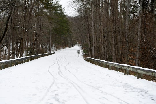 Tracks from shoes, dogs and bikes are seen on a closed section of the Blue Ridge Parkway after a snow in East Asheville on Dec. 9, 2018.