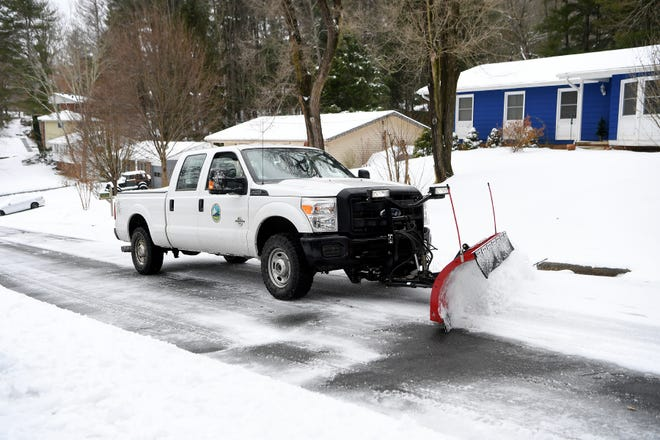 A Buncombe County snowplow clears snow on a road in Haw Creek on Dec. 9, 2018.