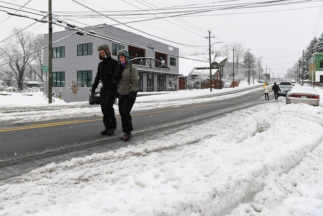 Alex Pietzsch, left, and his wife, Elizabeth, walk on Haywood Road to bypass snow-covered sidewalks in West Asheville Dec. 9, 2018.