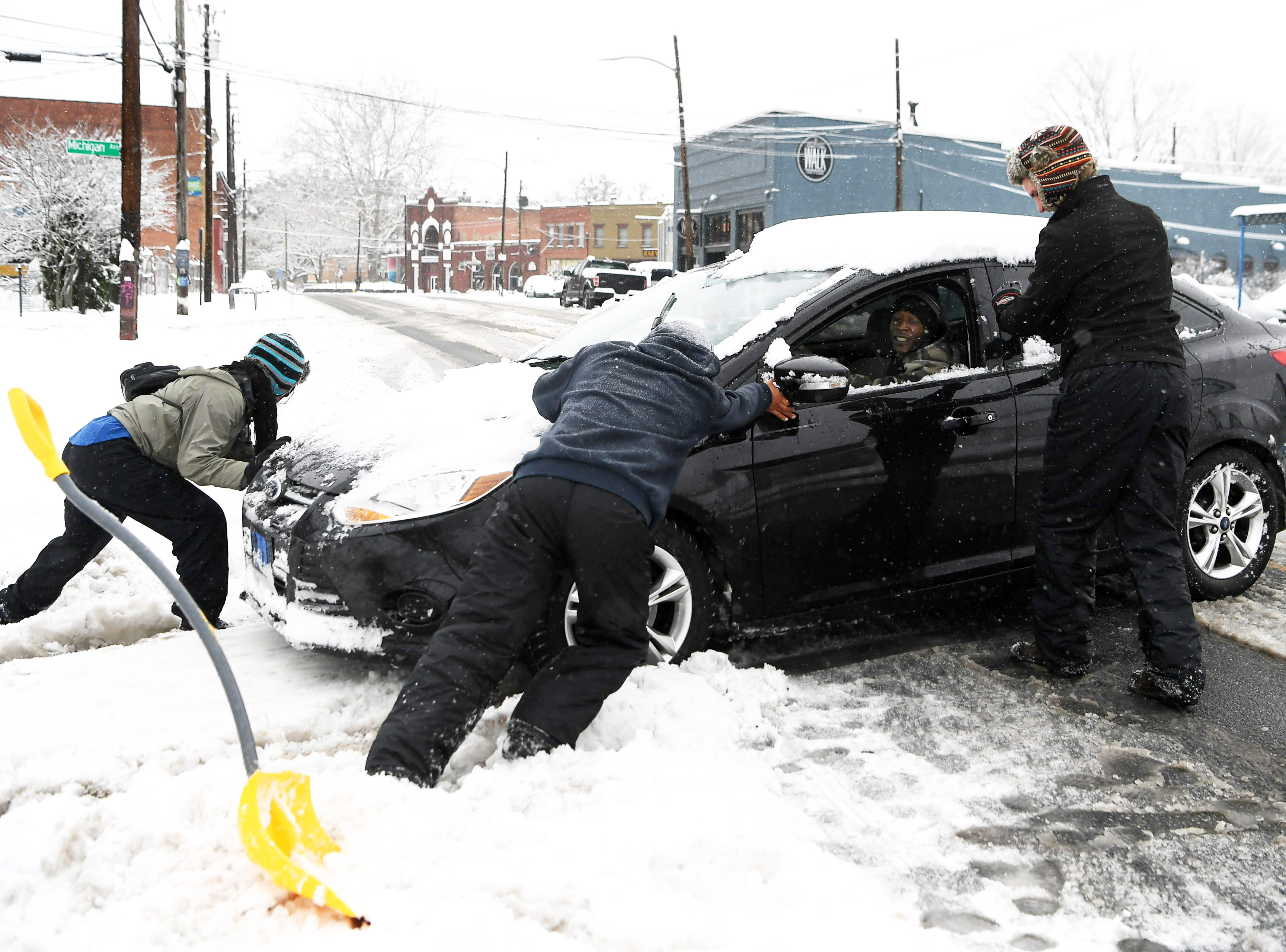From left, Elizabeth Pietzsch and Junior Bonilla help push JJ Thompson out of the snow at BJ's Food Mart in West Asheville Dec. 9, 2018. It was the third vehicle Bonilla helped dig out of the snow.