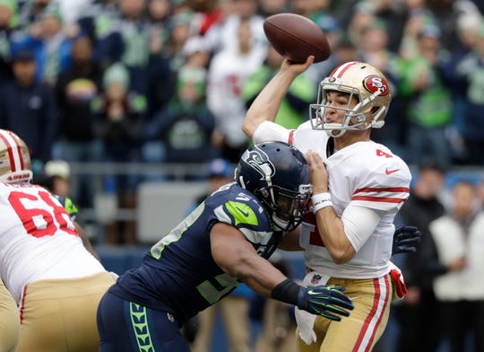 San Francisco 49ers quarterback Nick Mullens passes under pressure from Seattle Seahawks middle linebacker Bobby Wagner during the first half of an NFL football game, Sunday, Dec. 2, 2018, in Seattle.