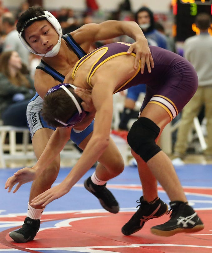 Olympic's Angelo Pangelinan grapples with Wenatchee's Toby Hambelton during the Olympic Duals at the Kitsap Sun Pavilion in Silverdale on Saturday, December 8, 2018.