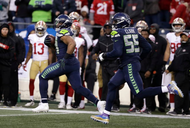 Seattle Seahawks middle linebacker Bobby Wagner, left, runs with defensive end Frank Clark (55) after intercepting a pass and running for a 98-yard touchdown against the San Francisco 49ers during the second half of an NFL football game, Sunday, Dec. 2, 2018, in Seattle.