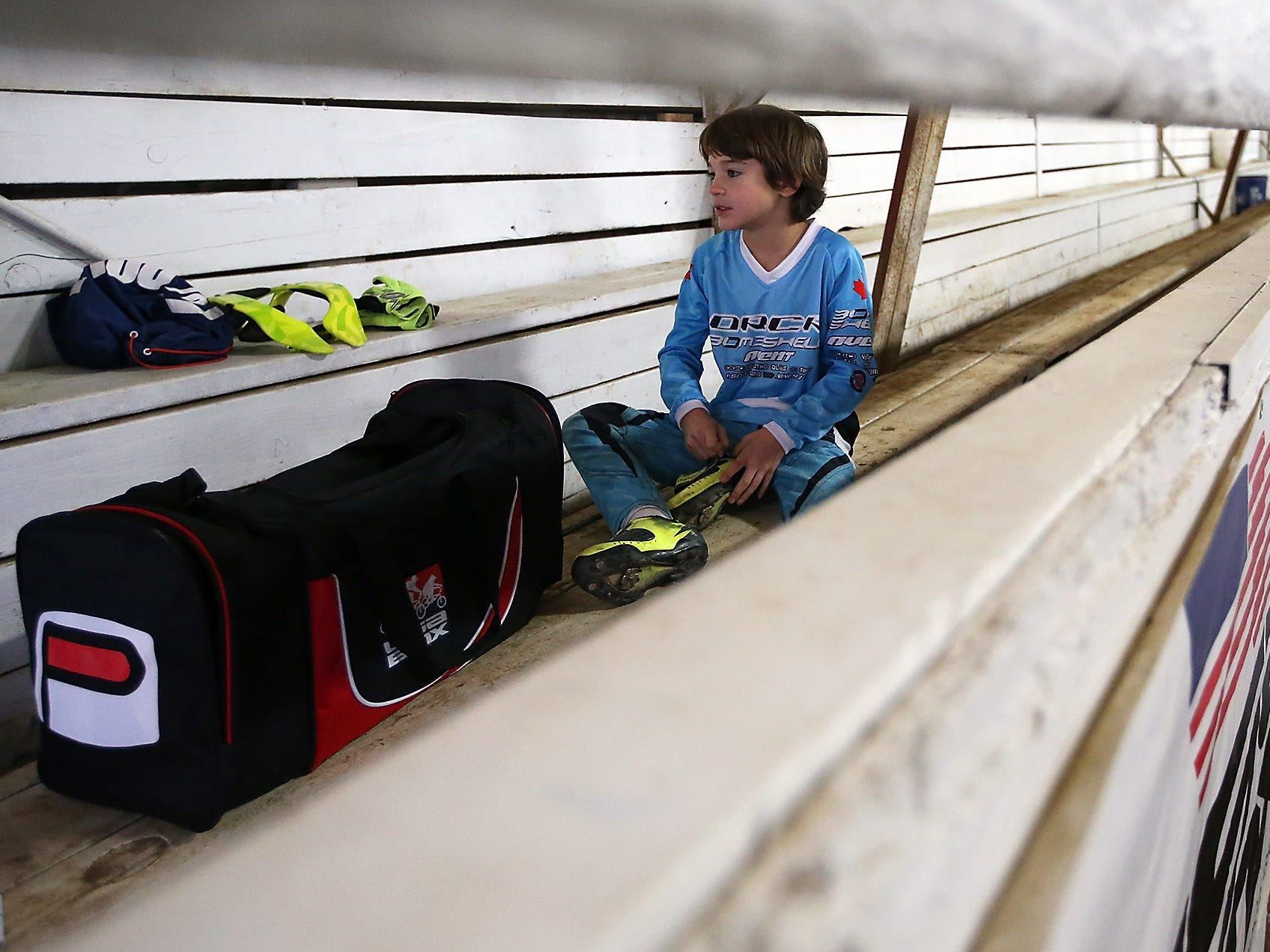 Wyatt Christensen, 6, of Kingston, puts on his shoes as he prepares to ride the track at Peninsula Indoor BMX in Port Orchard on Saturday, December 8, 2018.