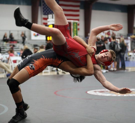 Central Kitsap's Shayne Hew-Len flips Mount Si's Braedon Haynie during their 132-pound bout Olympic Duals at the Kitsap Sun Pavilion on Saturday.