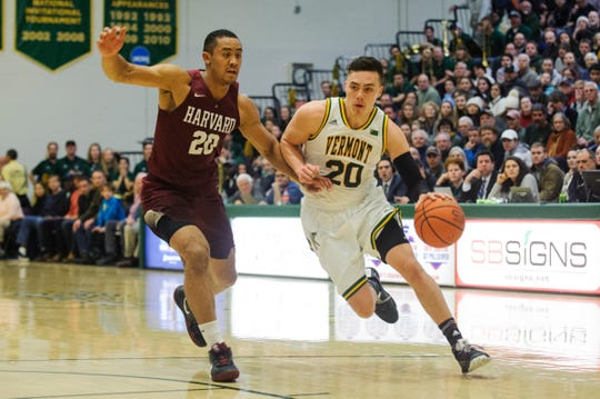 Vermont guard Ernie Duncan (20) drives to the hoop past Harvard's Justin Bassey (20) during the men's basketball between the Harvard Crimson and the Vermont Catamounts at Patrick Gym on Saturday night December 8, 2018 in Burlington.