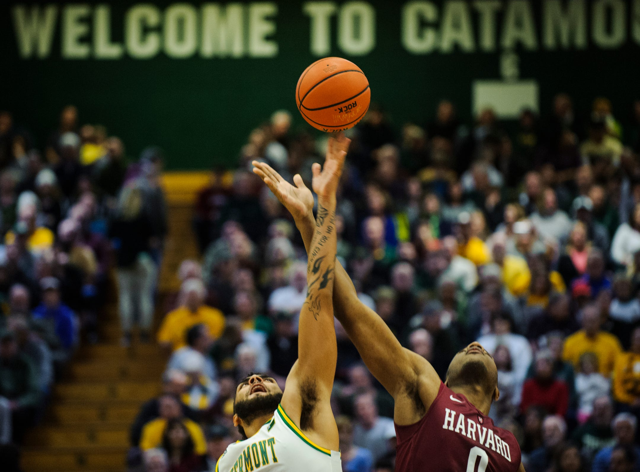 Vermont forward Anthony Lamb (3) and Harvard's Chris Lewis (0) battle for the opening tip off during the men's basketball between the Harvard Crimson and the Vermont Catamounts at Patrick Gym on Saturday night December 8, 2018 in Burlington.