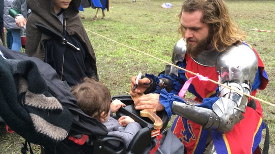 A knight signs a wooden sword for a small fan at the 20th annual Ingleside Renaissance Faire Saturday, Dec. 8, 2018.