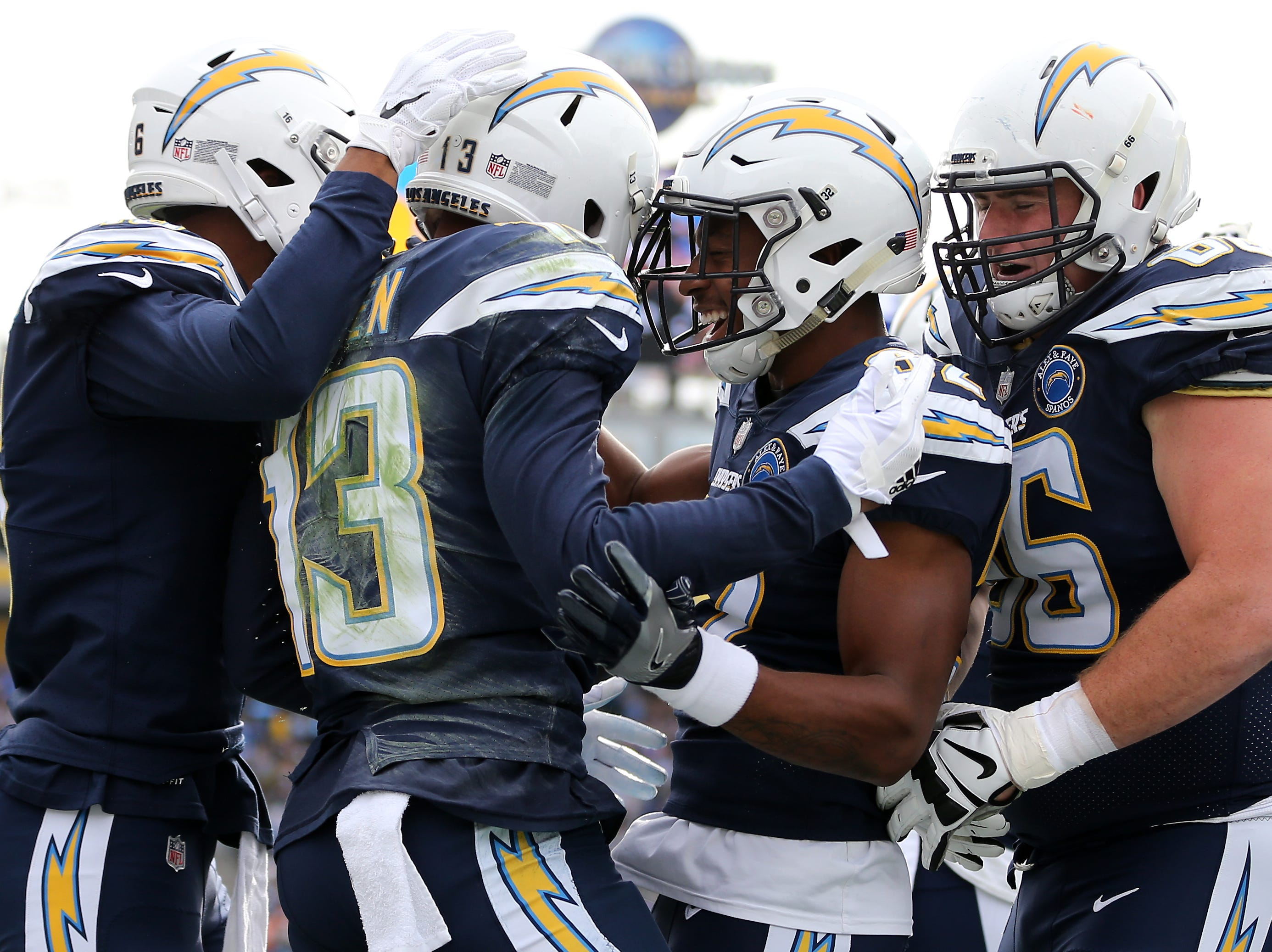 Los Angeles Chargers wide receiver Keenan Allen (13) is congratulated for his touchdown catch by Los Angeles Chargers running back Justin Jackson (32), second from right, and Los Angeles Chargers offensive guard Dan Feeney (66), far right, in the first quarter of a Week 14 NFL football game, Sunday, Dec. 9, 2018, at StubHub Center in Carson, California.