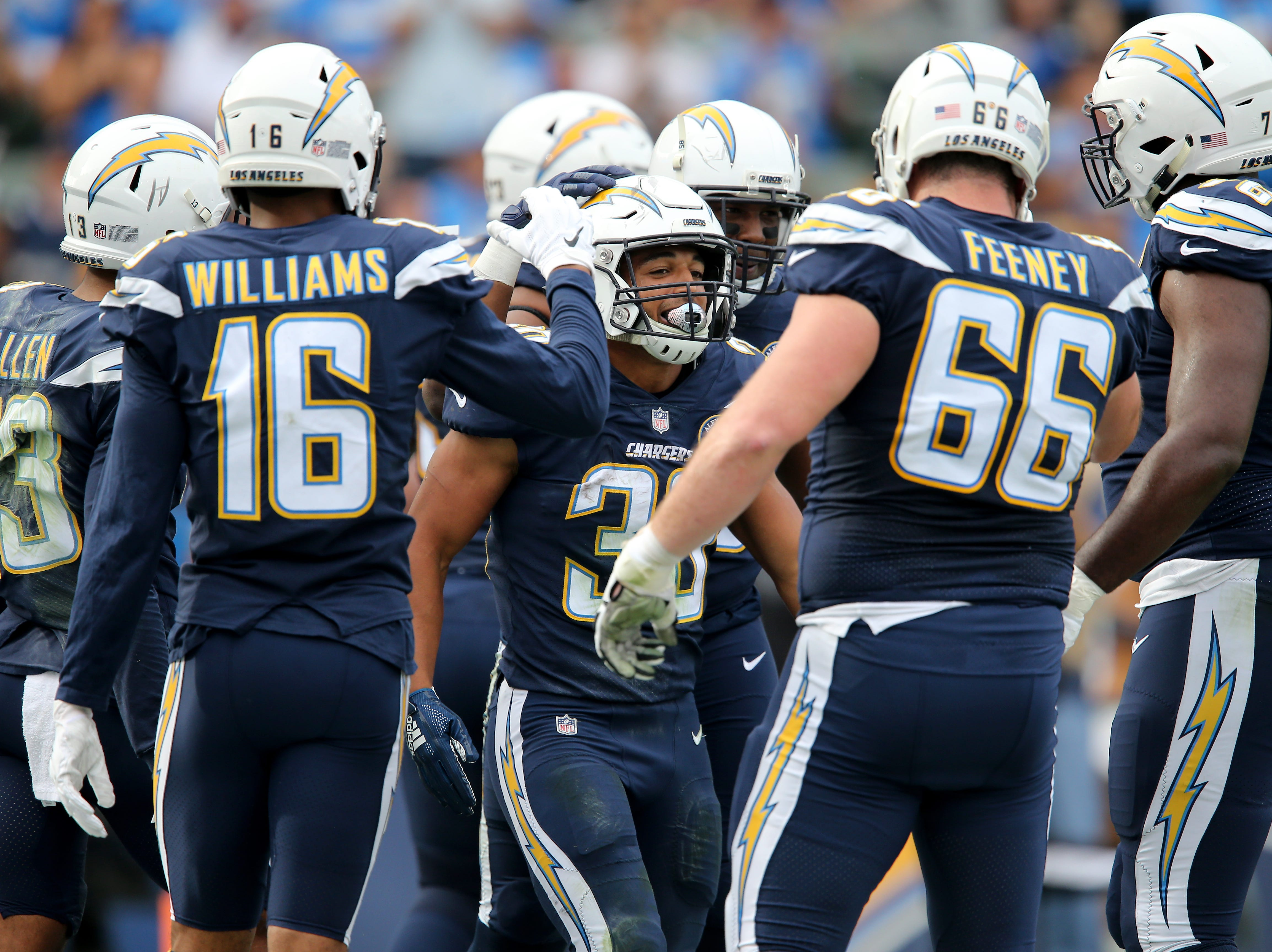 Los Angeles Chargers running back Austin Ekeler (30), center, is congratulated by teammates after scoring a touchdown in the first quarter of a Week 14 NFL football game Cincinnati Bengals, Sunday, Dec. 9, 2018, at StubHub Center in Carson, California.