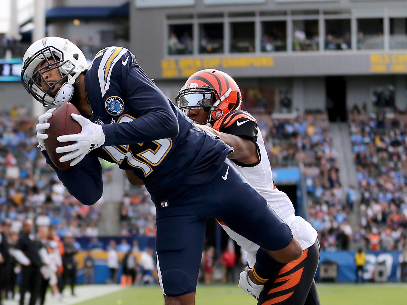 Los Angeles Chargers wide receiver Keenan Allen (13) catches a touchdown pass as Cincinnati Bengals defensive back Darqueze Dennard (21) defends in the first quarter of a Week 14 NFL football game, Sunday, Dec. 9, 2018, at StubHub Center in Carson, California.