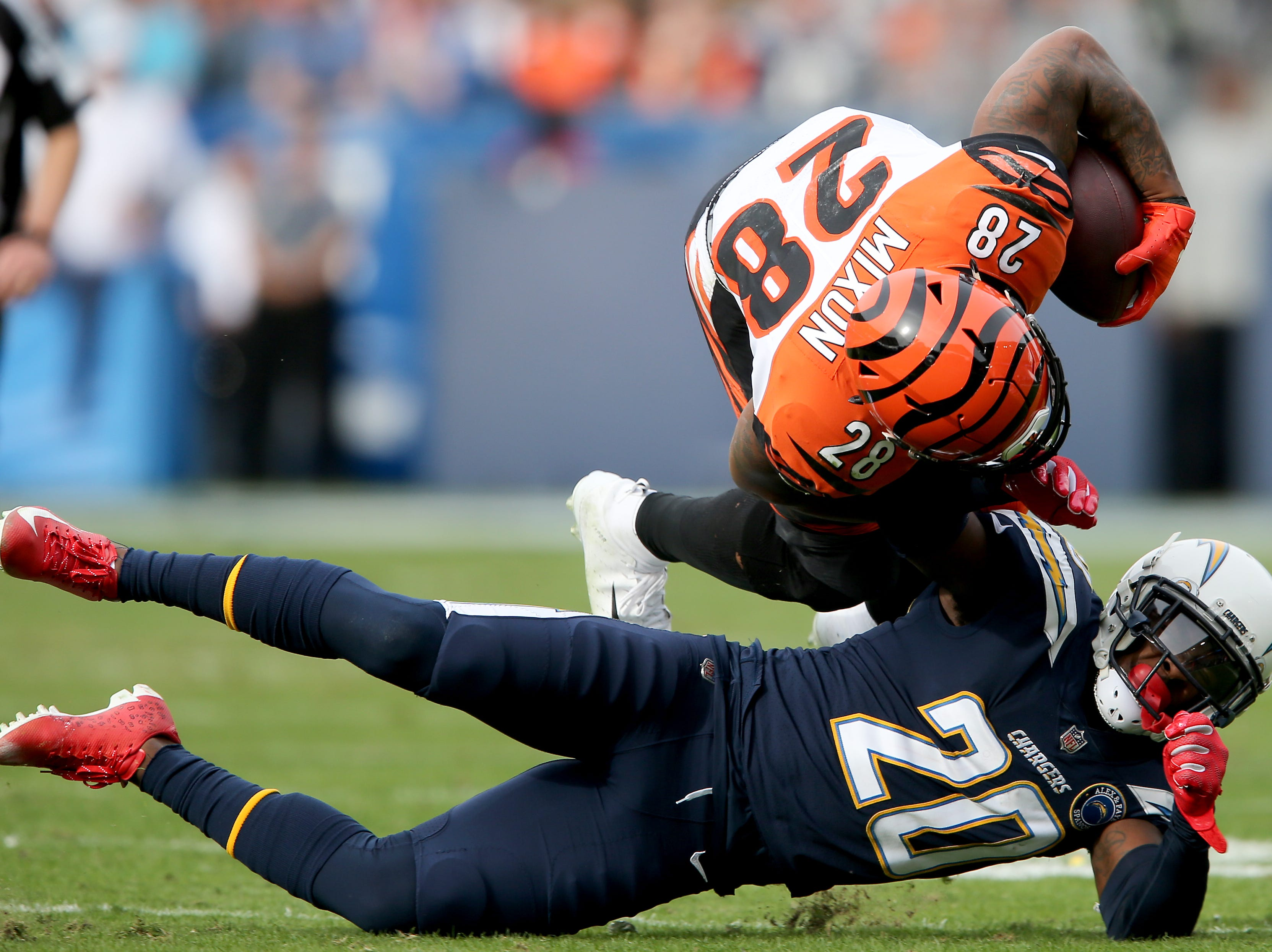 Cincinnati Bengals running back Joe Mixon (28) is upended by Los Angeles Chargers defensive back Desmond King (20) on a run in the first quarter of a Week 14 NFL football game, Sunday, Dec. 9, 2018, at StubHub Center in Carson, California.