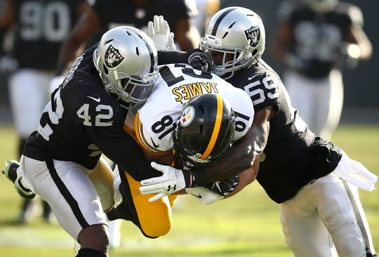 Jesse James is tackled by Raiders defenders last season.