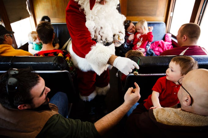 18 month old Raymond Shivers gets a bells from Santa, played by volunteer Roy Hogan, during the Santa Express at the Boone and Scenic Valley Railroads on Saturday, Dec. 8, 2018, in Boone.
