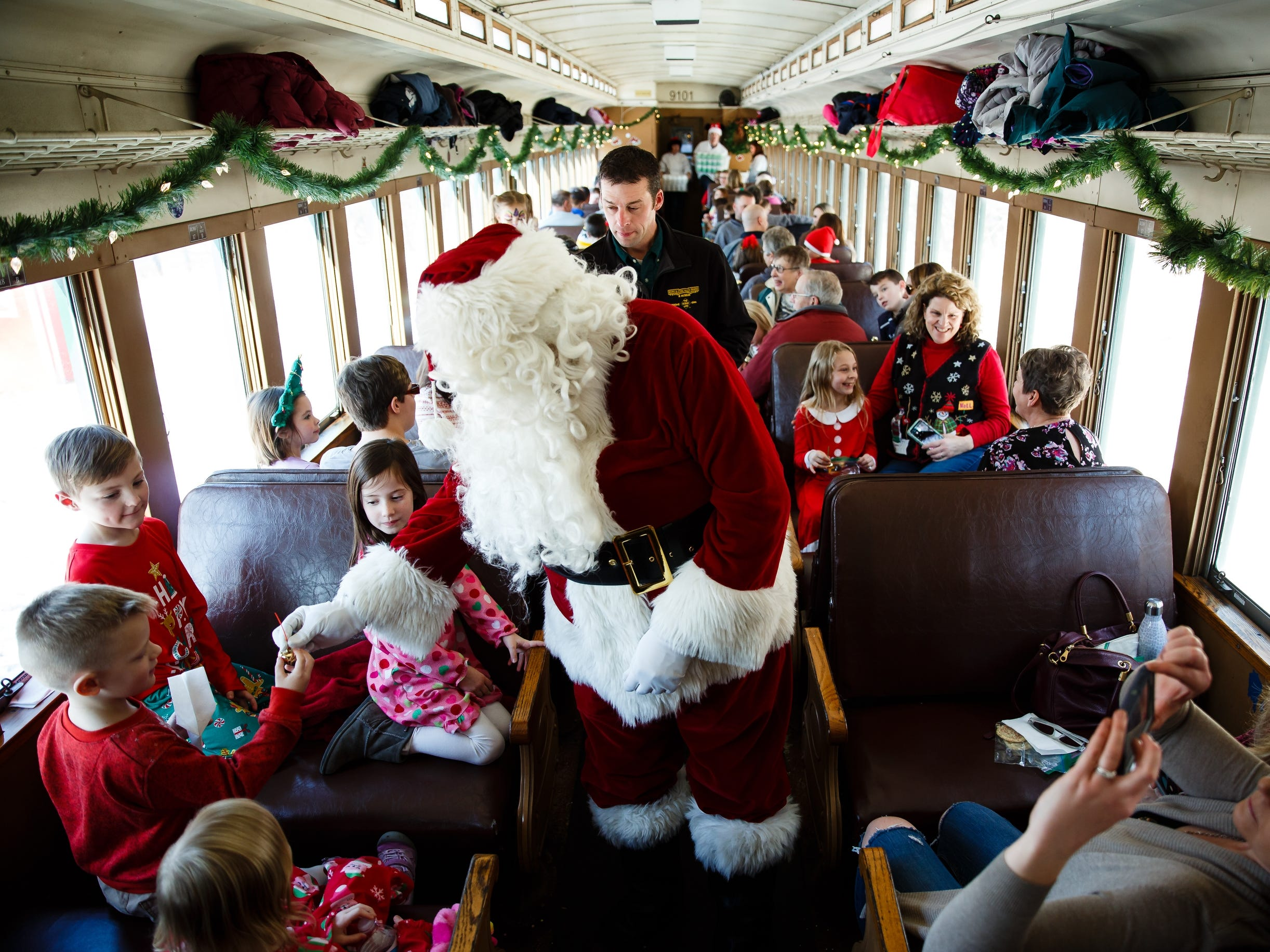 Children get bells from Santa, played by volunteer Roy Hogan, during the Santa Express at the Boone and Scenic Valley Railroads on Saturday, Dec. 8, 2018, in Boone.