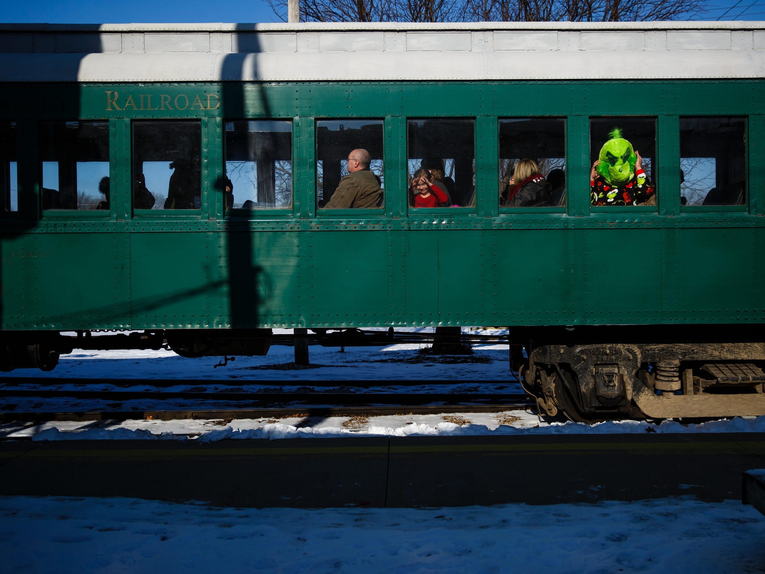 Sam Schneider, 7, Shell rock, looks out the window as Henry Knapp of Panora, dressed as the Grinch, finds his seat on the Santa Express train at the Boone and Scenic Valley Railroads on Saturday, Dec. 8, 2018, in Boone.