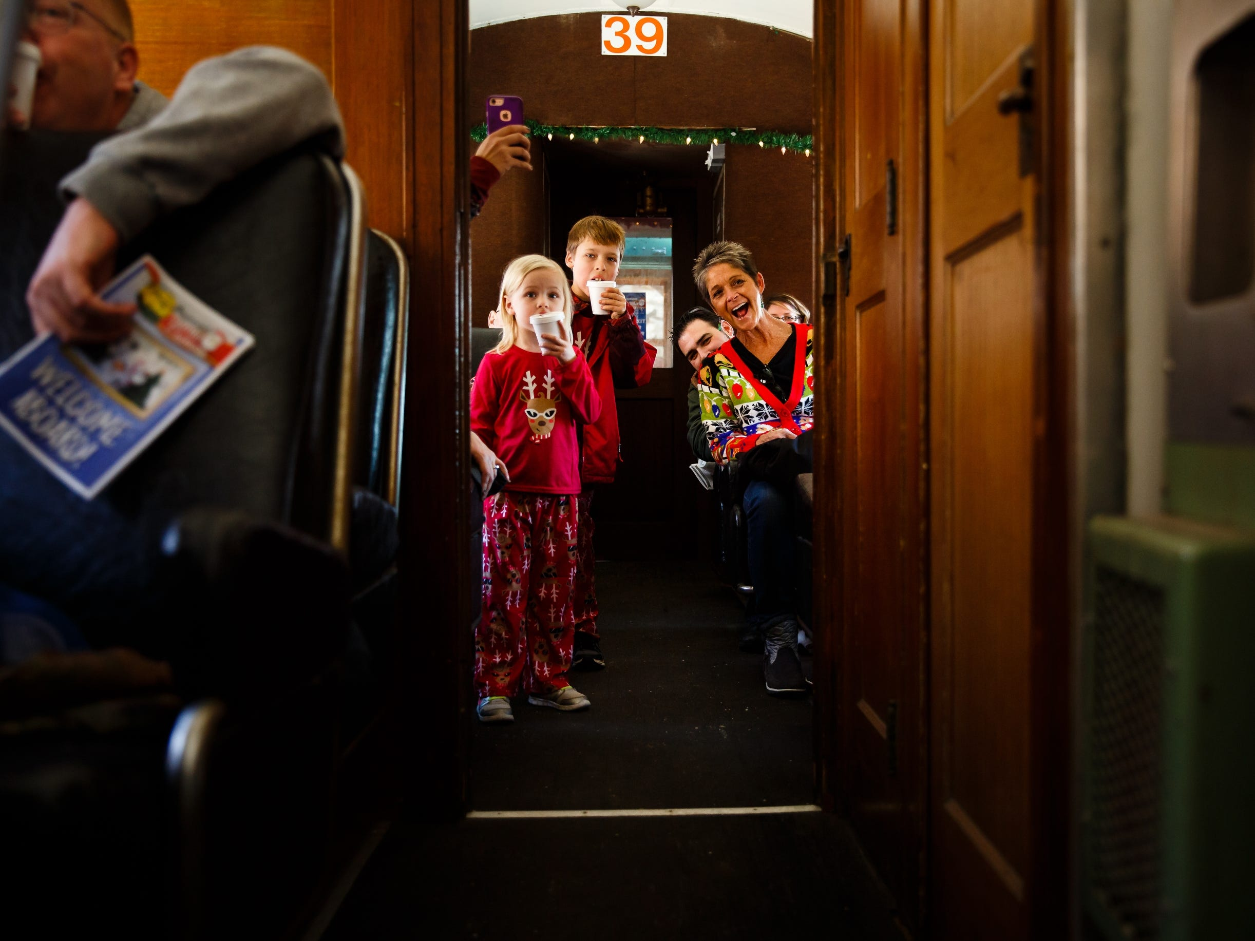 "Braya Strope, 4, and brother Deacon Strope, 8, of Mount Vernon stand as ""Santa"" makes his way through their train car during the Santa Express at the Boone and Scenic Valley Railroads on Saturday, Dec. 8, 2018, in Boone."
