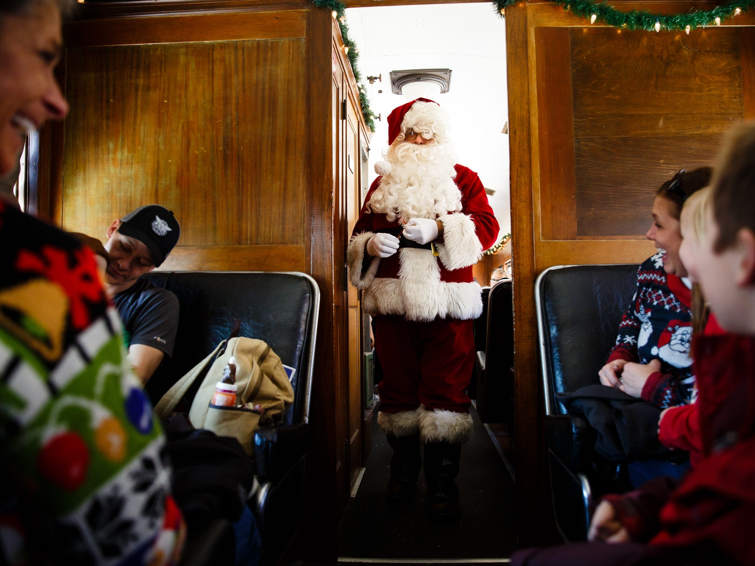 Santa, played by volunteer Roy Hogan, makes his way through a train car handing out bells during the Santa Express at the Boone and Scenic Valley Railroads on Saturday, Dec. 8, 2018, in Boone.