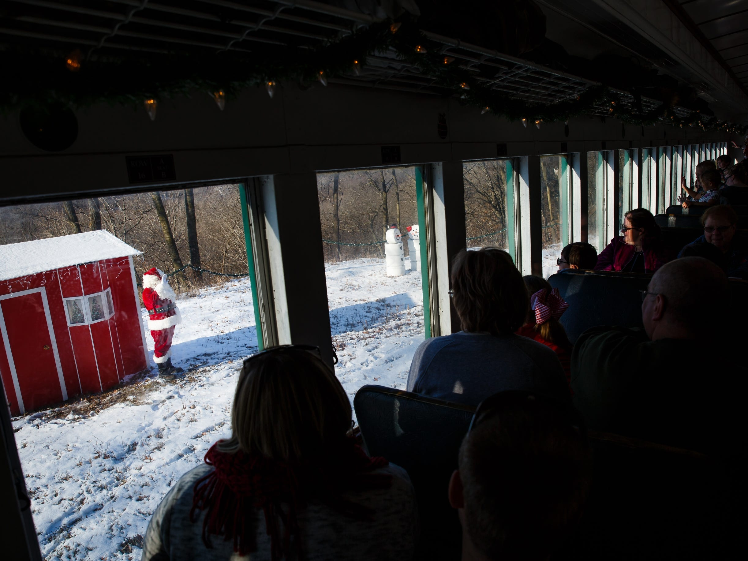 "Santa, played by volunteer Roy Hogan, waves to Santa Express train riders from the ""North Pole"" during the Santa Express train ride at the Boone and Scenic Valley Railroads on Saturday, Dec. 8, 2018, in Boone."