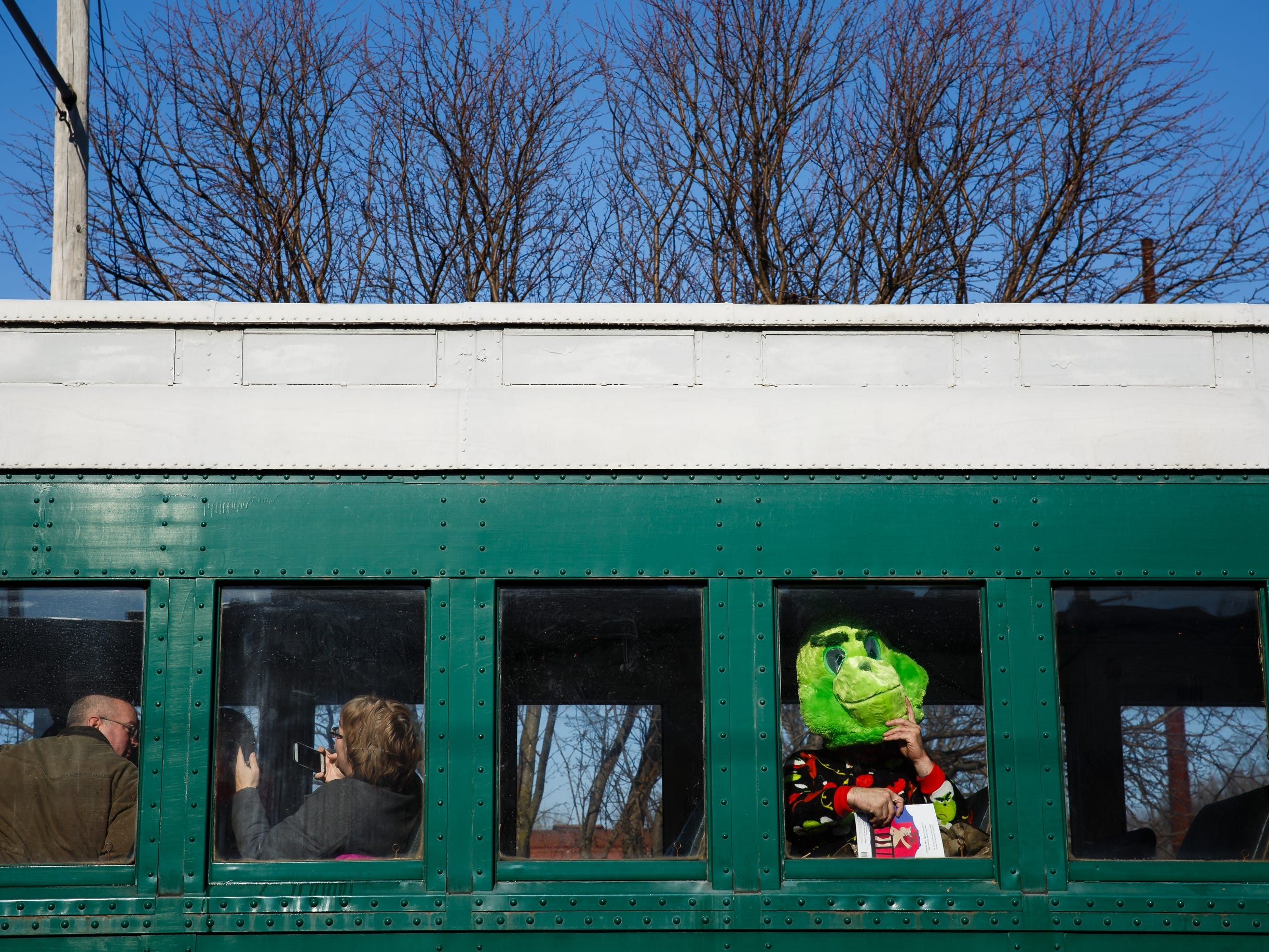 Dressed as the Grinch, Henry Knapp of Panora finds his seat on the Santa Express train at the Boone and Scenic Valley Railroads on Saturday, Dec. 8, 2018, in Boone.