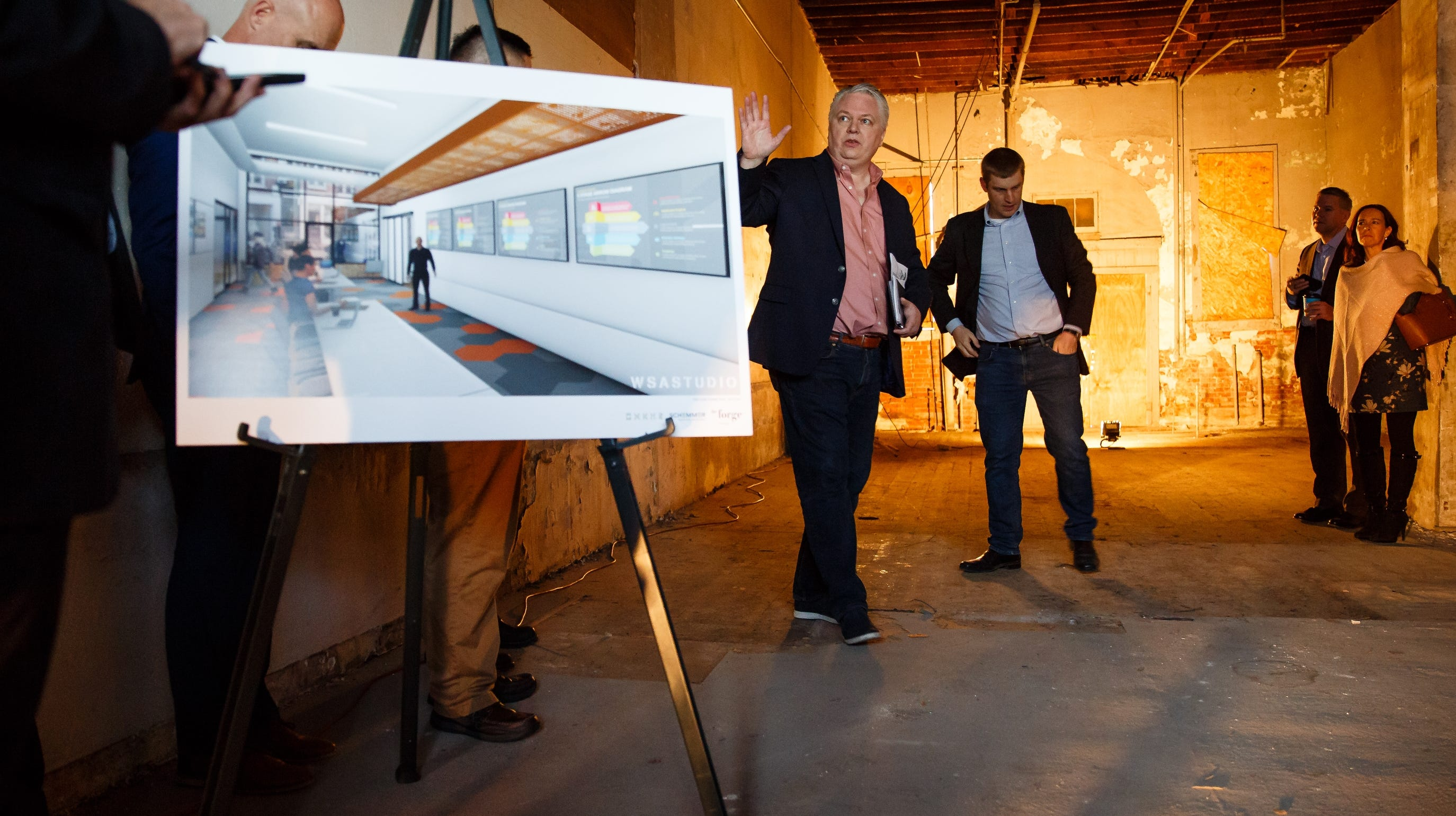 Linc Kroeger with Pillar Technology, center, and Mechanical engineer Chris Deal show off a rendering to a crowd, including Silicon Valley leaders who came to see the building that will eventually house Pillar Technology on Saturday, Dec. 8, 2018, in Jefferson.