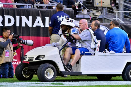 Ziggy Ansah leaves the field with a shoulder injury in the first half against the Cardinals.