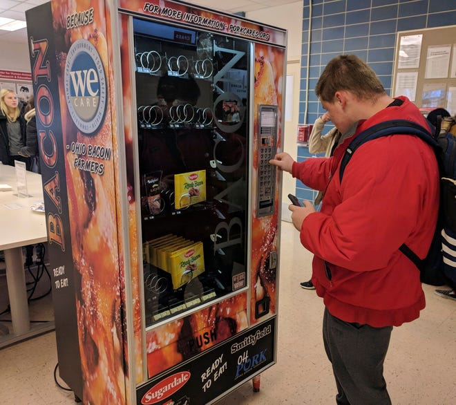 This Dec. 7, 2018, photo shows Ohio State University sophomore Nick Vales buys a package of bacon slices from a vending machine available on the Columbus campus.  The machine offers cooked bacon strips and bacon bits for $1.