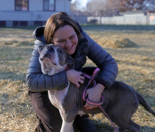Gina Freemon, founder of  C.H.A.I.N.E.D., hugs a stray pit bull picked up by her team of volunteers on Sunday, December 9, 2018 in S.W. Detroit.