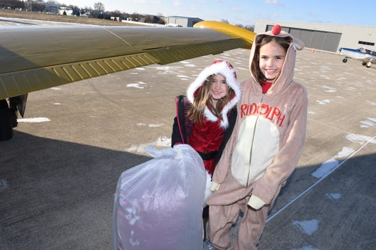 Trisha Sedine and her sister Taya Sedine dressed as Mrs. Claus and Rudolph as they loaded a plane with Christmas gifts for delivery.