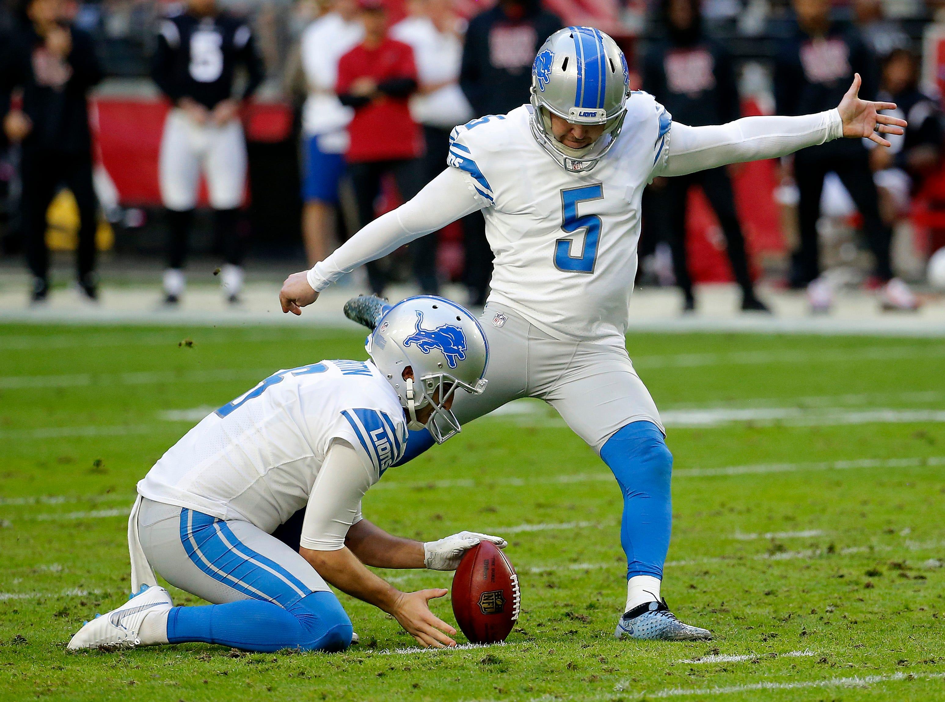 Detroit Lions kicker Matt Prater (5) kicks a field goal against the Arizona Cardinals as punter Sam Martin holds during the first half.