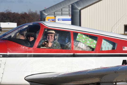 Pilot Dick Lawrence gives a thumbs up — Santa style — as he prepares for take off.