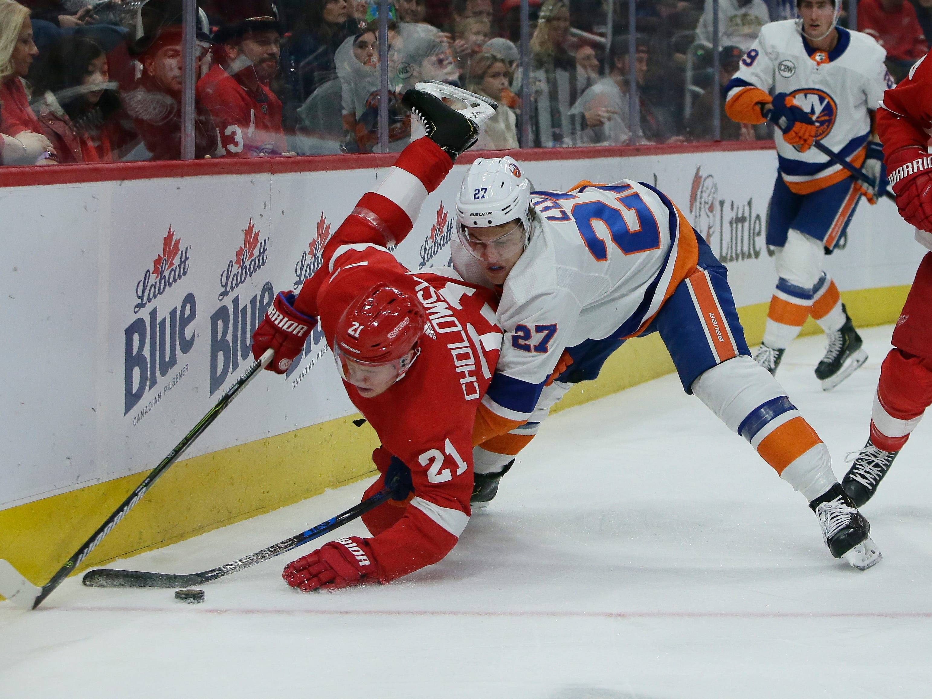 New York Islanders left wing Anders Lee (27) tries to steal the puck from Detroit Red Wings defenseman Dennis Cholowski (21) during the first period.