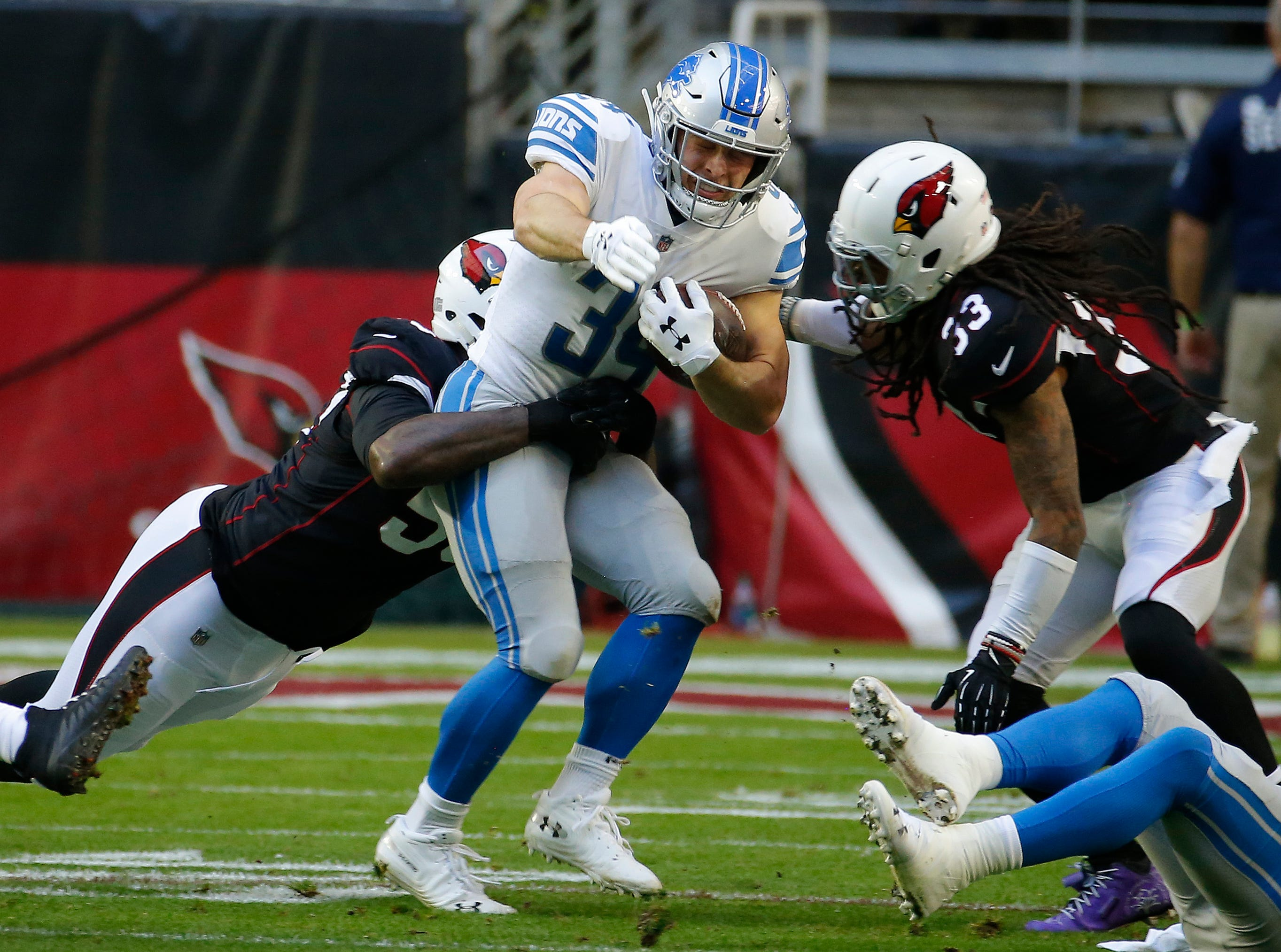 Detroit Lions running back Zach Zenner (34) is hit by Arizona Cardinals defensive end Zach Moore, left, during the first half.