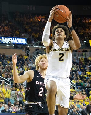 Michigan's Jordan Poole, right, drives to the basket as South Carolina's Fahmmi Mamo gives chase during the second half on Saturday.