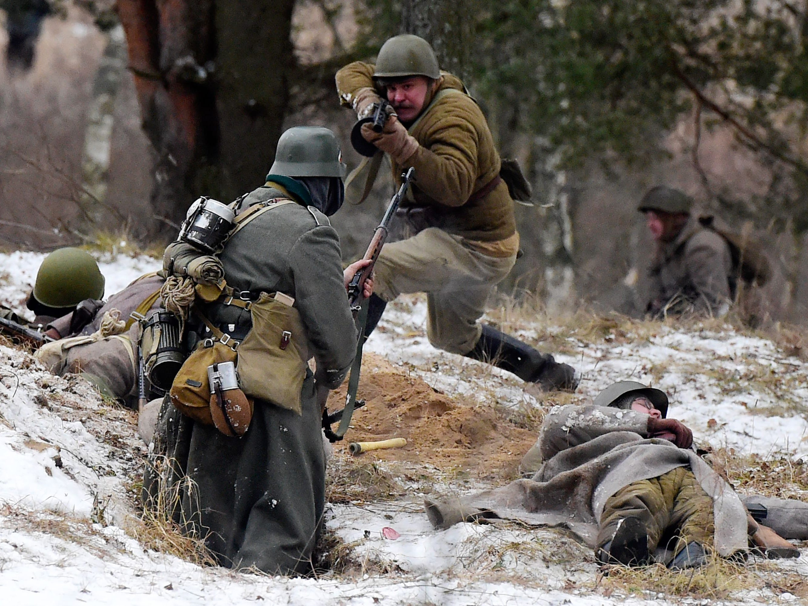 Members of a historical military club, wearing Soviet and Nazi uniforms, participate in a World War II battle re-enactment marking the Fatherland Heroes Day near Kirovsk, outside Saint Petersburg on December 9, 2018.