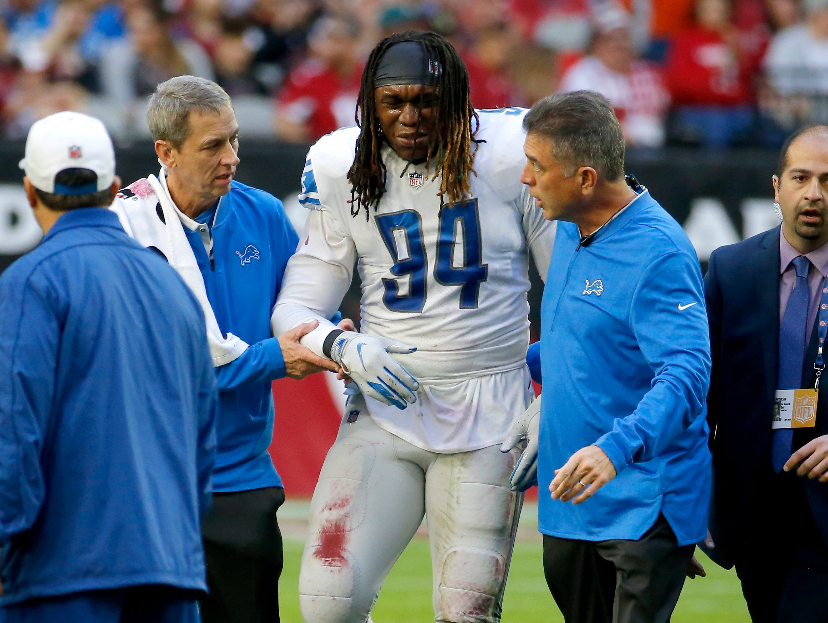 Detroit Lions defensive end Ezekiel Ansah (94) is helped after an injury against the Arizona Cardinals during the first half.